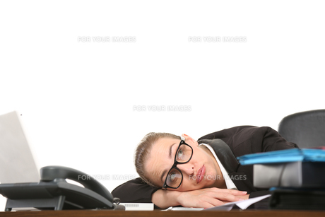 secretary lying with her head on the desk exhaustedの素材 [FYI00712577]