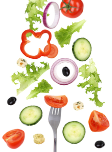 falling eating salad with fork,tomato,cucumber and pepperの写真素材 [FYI00715852]