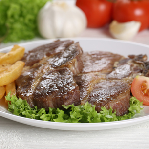 steaks from pork meat with fries and salad on plateの写真素材 [FYI00715867]