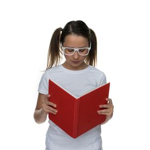 Young schoolgirl in glasses standing readingの写真素材 [FYI00716353]