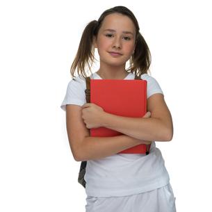 Young schoolgirl clutching a text bookの写真素材 [FYI00716356]