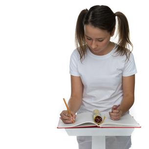 Young schoolgirl writing class notesの写真素材 [FYI00716359]