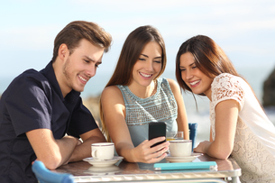 Group of friends watching social media in a smart phoneの写真素材 [FYI00716976]