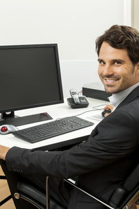young successful businessman with black suit in the officeの写真素材 [FYI00718368]