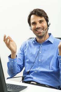 attractive young man with headset in the office customer service operatorの写真素材 [FYI00718373]