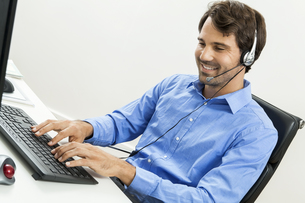 attractive young man with headset in the office customer service operatorの写真素材 [FYI00718374]