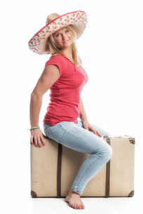 blonde woman with sombrero sitting on a suitcaseの写真素材 [FYI00718626]