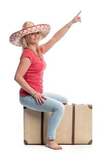 a woman sitting on a suitcase and pointing upwardsの写真素材 [FYI00718628]