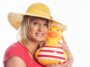 blond woman wearing a straw hat holds a large rubber duckの素材 [FYI00718644]