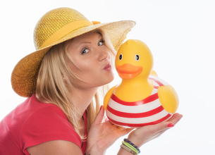 a woman wearing a straw hat kissing a rubber duckの素材 [FYI00718646]