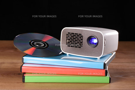 mini projector with dvd and dvd cases on wooden table with black backgroundの写真素材 [FYI00719770]