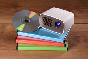 mini projector with dvd and dvd cases on wooden tableの写真素材 [FYI00719771]