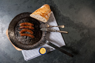 4 nuremberg sausages with sauerkraut in a gu?eisenpfanne on a wooden board with bread and mustard. seen from above arranged on a slate and a cloth.の写真素材 [FYI00721249]