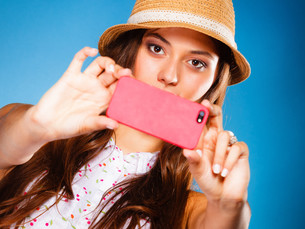 woman taking self picture with a smartphone cameraの写真素材 [FYI00726139]
