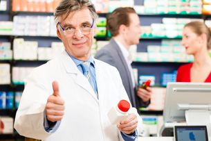pharmacist in his pharmacy with customersの写真素材 [FYI00728705]