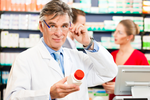 pharmacist in his pharmacy with customersの写真素材 [FYI00728707]