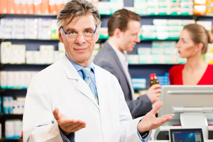 pharmacist in his pharmacy with customersの写真素材 [FYI00728708]