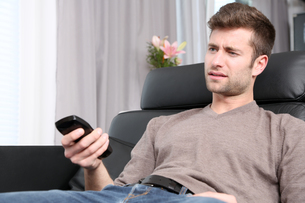 young man sitting on the couch annoyedの素材 [FYI00729927]