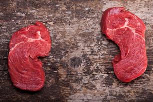 two raw steaks on a wooden boardの写真素材 [FYI00731668]