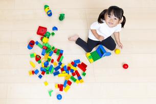 フローリングでブロック遊びをしながら見上げる幼い女の子の写真素材 [FYI00735486]