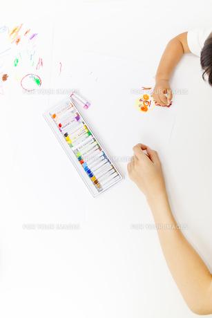 お絵描きをする幼い女の子と成人女性の手の写真素材 [FYI00736159]