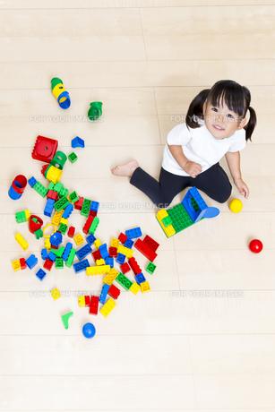 フローリングでブロック遊びをしながら見上げる幼い女の子の写真素材 [FYI00736162]