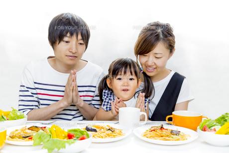 幼い女の子と食事を始める家族の写真素材 [FYI00736178]