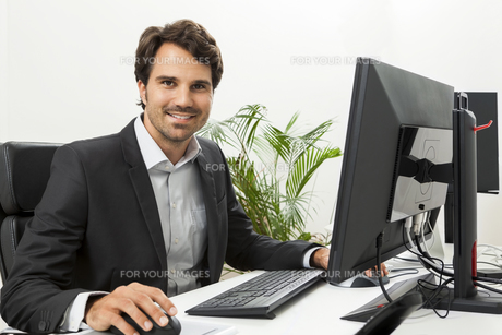 young successful businessman with a black suit in the officeの素材 [FYI00739492]