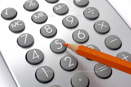 finance and costing with red pencil and calculator yields savings and reductionの写真素材 [FYI00740161]