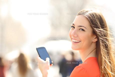 Happy woman walking in the street using a smartphoneの写真素材 [FYI00740283]