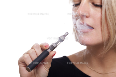 young woman smoking a e-cigarette with blonde hair portraitの素材 [FYI00740396]