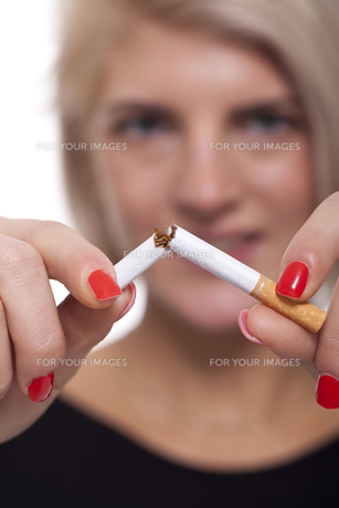 young blonde woman breaks a cigarette stop smokingの素材 [FYI00740406]