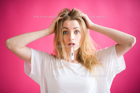 blonde woman with clinical thermometer tearing her hairの素材 [FYI00740837]