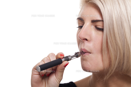young woman smoking a e-cigarette with blond hair portraitの写真素材 [FYI00740988]