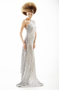 Vogue Style. Trendy Woman in Silver Silky Dress and Creative Hairstyleの写真素材 [FYI00741272]