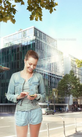 Smiling Woman with Headset on the Streetの写真素材 [FYI00741306]