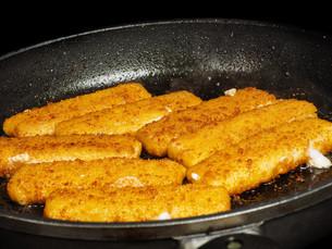 Closeup of crispy breaded fish fingers in hot fry panの写真素材 [FYI00742276]