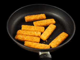Crumbed fish fingers in fry pan, isolated on blackの写真素材 [FYI00742285]