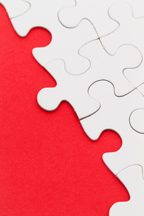 Blank white jigsaw puzzles on a bright red paper backgroundの写真素材 [FYI00742324]