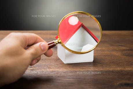 Person Hand With Magnifying Glass And Miniature Houseの素材 [FYI00743067]