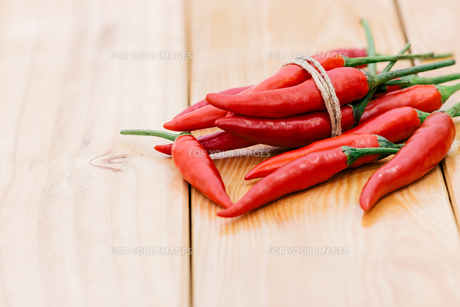 closeup red chili peppers spice ingredient on wood tableの写真素材 [FYI00743350]