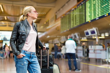 Female traveller checking flight departures board.の素材 [FYI00743441]