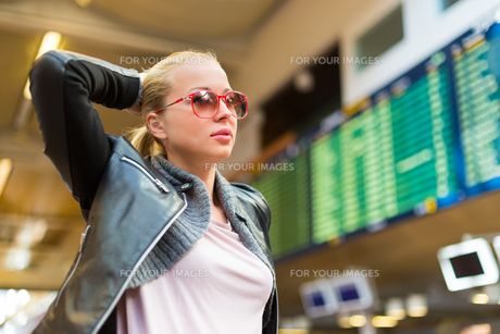 Female traveller checking flight departures board.の素材 [FYI00743443]
