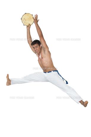 Capoeira, Brazilian Man jumping with tambourineの写真素材 [FYI00743713]