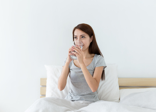 Woman drinking water on the bedの写真素材 [FYI00743853]