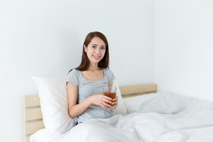 Asian young woman holding a tea and sitting on bedの写真素材 [FYI00743856]