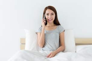 Woman talk to mobile and sitting on bedの写真素材 [FYI00743857]