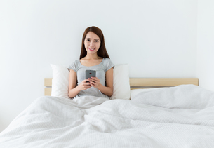 Asian young woman using cellphone on bedの写真素材 [FYI00743859]