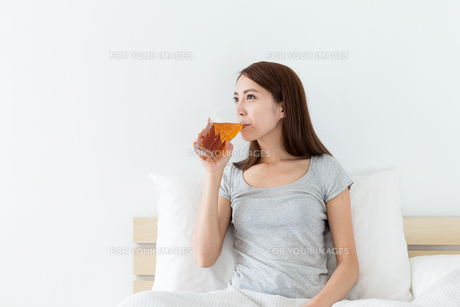 Chinese woman drink a cup of tea on bedの写真素材 [FYI00743863]