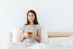 Asian woman holding a cup of tea and sitting on bedの写真素材 [FYI00743871]
